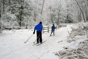 couple cross-country skiing on romantic trail
