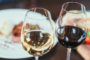 close-up view of two glasses with red and white wine on table in restaurant
